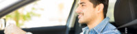 Portrait of handsome young latin man driving a car and smiling